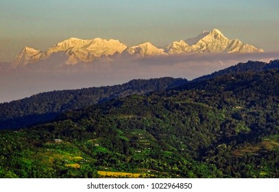 Changing colors of the snow capped peaks of Kanchenjunga (also spelled as Kangchenjunga) ranges, with shadows falling on the foothills beneath