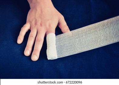 Changing dressing on hands. Wrap the bandage on the finger wound.