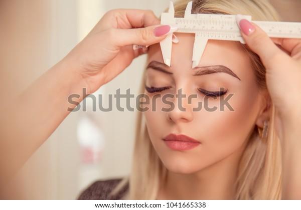 眉の形を変更する定規で眉を測るスタイリスト。美容院の微小色素沈着の仕事の流れ。目の眉をしぼった女性。