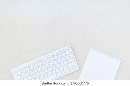 Changing table, white wireless keyboard and notebook with blank sheet on a wooden surface. Copy space