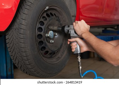 Changing the wheel with an impact wrench. Close up of man's hands changing wheel. Hands holding a impact wrench.