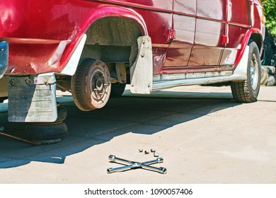 Changing a wheel on an old vintage a bit rusty red van at outdoor car service