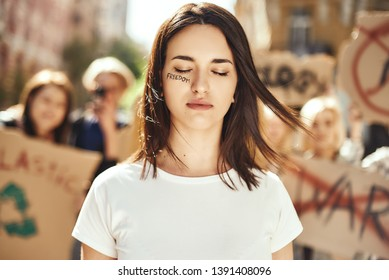 Changing the world. Young and brave woman with word freedom written on her face and with closed eyes standing around female activists on the road during protest march