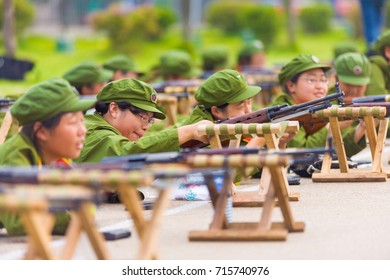 Changsha, China - September 5, 2007: Female Chinese university students drill in prone face-down positions with rifles during compulsory military training