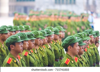 Changsha, China - September 5, 2007: Rows of male Chinese university students in communist green uniforms line up in formation for compulsory military training