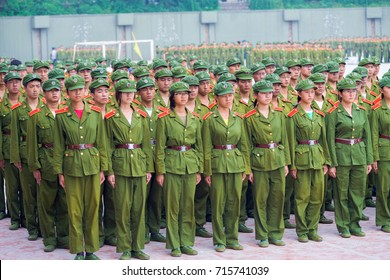 Changsha, China - September 5, 2007: Male and female Chinese university students in green uniforms line up in formation for compulsory military training