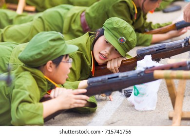 Changsha, China - September 5, 2007: A young relaxing Chinese female university student shows apathy and disinterest at rifle drills during compulsory military training