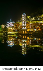 Changsha,China Feb 20, 2014 night illumination lights of FengHuang village chinese ancient pagoda reflect on river water