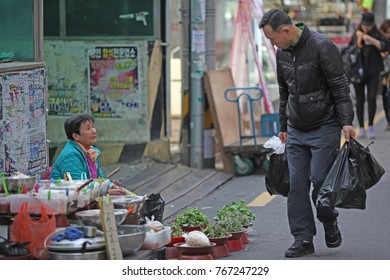 Changwon, South Korea - March 19, 2013: A man walks by a street vendor in South Korea. Elderly women often rely on income from selling fruits and vegetables in cities and towns.