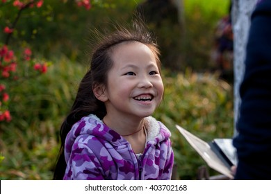 CHANGZHOU,CHINA-MAY 20:Unidentified girl on garden for take picture for winter season on May,2016 in Changzhou in jiangsu china. The girl wear violet coat take picture by telephone by her mom.