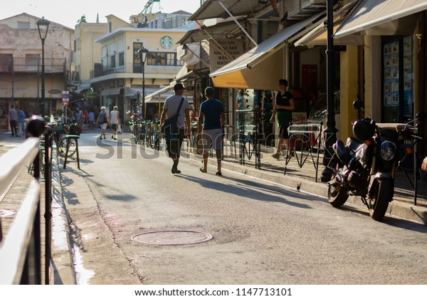 Chania, Crete, Greece - August 2017: Two persons walking down a street as the sun is setting.