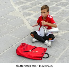 Chania, Crete. Greece - October 21, 2017:  Young boy in red football strip, sitting cross legged on a pavement. Playing a doumbek, busking in the harbour area. Holdall with loose change in front.