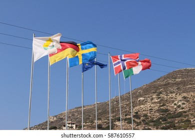 CHANIA, CRETE ISLAND, GREECE - JULY 31, 2016: Partly torn, fluttering national flags (respectively Cyprus, Germany, Sweden, European Union, Norway, Italy) in windy Falassarna Beach.