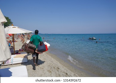Chaniotis, Greece - July 08 2017: Vendor with counterfeit products on the beach.Street vendor selling popular brands replicas bags by a Greek beach shore on a sunny summer day.