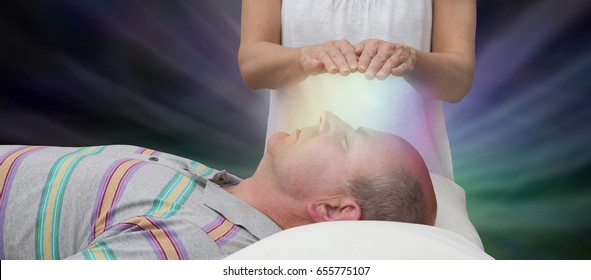 Channeling Healing Energy - female with hands held six inches above a male patient's face displaying colored light on a dark background