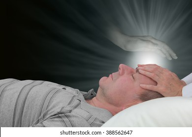 Channeling healing with a spirit guide - female hands laid on a male patient's forehead with an ethereal ghostly spirit hand hovering above and a glow of healing light  energy on a dark background