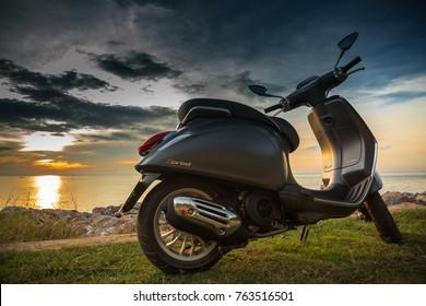 CHANTABURI,THAILAND - NOVEMBER 26,2017 : New Vespa Italian designed scooter is parking at coastal road in sunset time