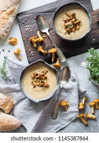 Chanterelle cream soup in blue bowls and baguette on the rustic table and wood board. Autumn food concept. Top view