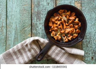 Chanterelle mushrooms fried in cast iron pan with linen cloth on blue background. Healthy vegetarian food