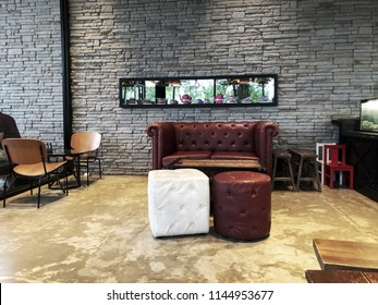 Chanthaburi, Thailand; 27 July 2018: Modern cafe interior with a brick wall, a wooden tables, white sofas. The interior design of a Coffee shop, cafe.