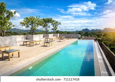 chanthaburi, thailand - august 26 2017:Swimming pool on top of roof deck building and sunny reflections with teak wood flooring stripes summer vacation