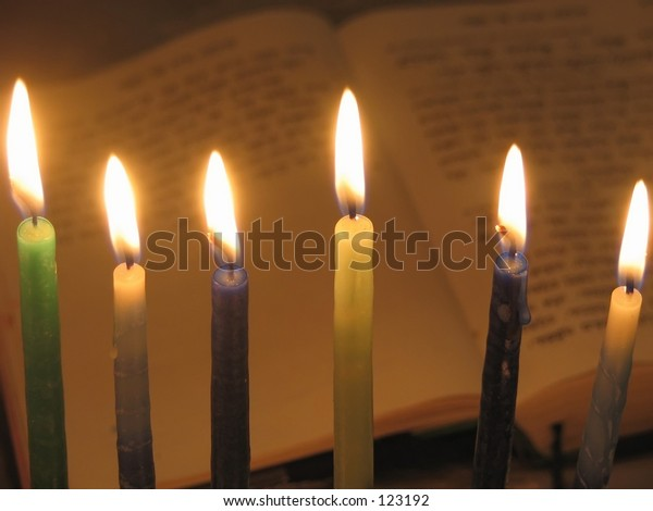 Chanukah candles with prayer book in background
