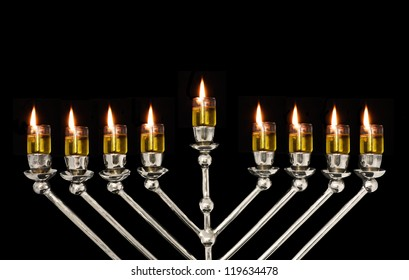 Chanukah oil menorah close up. Lighted oil menorah for the Jewish holiday of Chanukah. Small glass cups hold olive oil in which the wicks are placed and then lit; isolated on a black background.