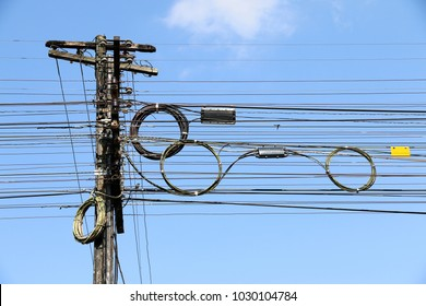 chaos of fiber optic and telephone cables on electric pole