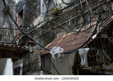 chaotic layed electric wires between weathered buildings in a old town