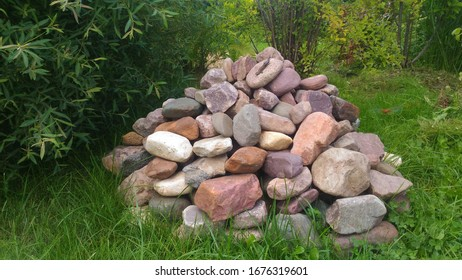 Chaotic pyramid of different size stones in pastel shades on the grass with a part of the willow on the left and a lizard on one of the upper stones against a background of green plants