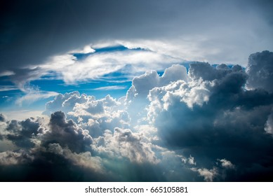 Chaotic Sky Cumulonimbus and towering Cumulus clouds resulting in heavy rain and hail-showers seen from an altitude of 10.000 feet with a friendly blue spot at the end of the cloud tunnel.