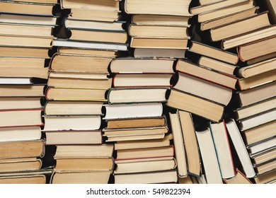 chaotic stack of old books background, selective focus