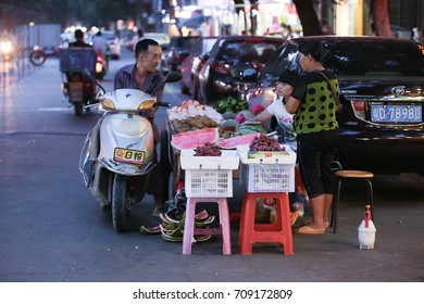 CHAOZHOU, CHINA - JULY 31, 2014 : Local customer bargaining with a fruit hawker at a night market in Chaozhou town, Guangdong, China.