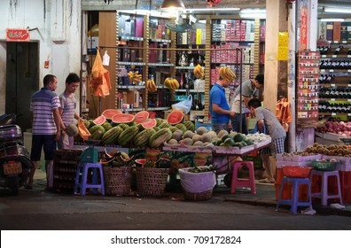 CHAOZHOU, CHINA - JULY 31, 2014 : A grocery store shopkeeper selling various fresh fruit at Chaozhou town, Guangdong, China.