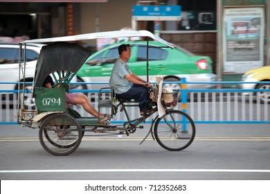 CHAOZHOU, CHINA - JULY 31, 2014 : A driver riding modified electric trishaw carrying passengers cruising along Chaofeng road at Chaozhou town, Guangdong, China.