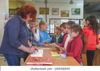 Chapaevsk, Samara region, Russia - May 10, 2019: Elementary school. Woman Teacher with primary school students. School children are standing next to the teacher's desk