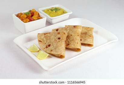 Chapati or Indian flat bread, is a healthy, and vegetarian food, eaten for breakfast, lunch or dinner, with dal and chana dal masala as side dishes, on a plate.