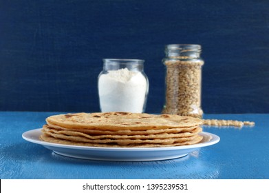 Chapati or Indian flat bread, which is a traditional and popular vegetarian breakfast or lunch item, and in the background are wheat and wheat flour each in a bottle.