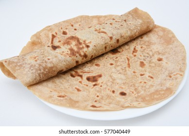 Chapati roti/chapathi/fulka/paratha Indian whole wheat flat bread. Healthy fiber rich traditional North/South food Kerala India. Spicy dal/dhal/daal curry fry side dish. split pea in mud/clay plate.