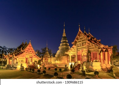 Chapel and golden pagoda at Wat Phra Singh Woramahawihan in Chiang Mai at twilight or night with stars in sky