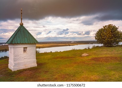 Chapel in Konstantinovo, Moscow region, Russia. Dramatic sunset cloudy sky and river Oka in background and meadow in foreground.