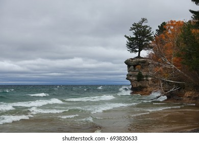 Chapel Rock, a famous rock formation at Pictured Rocks National Lakeshore, in the fall against a cloud filled sky and rough Lake Superior.