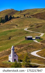 Chapel of San Maurizio at Passo Gardena, South Tyrol, Italy.  View to path to small white chapel San Maurizio and Dolomiti mountain. San Maurizio chapel on the Gardena Pass, South Tyrol, Italy.