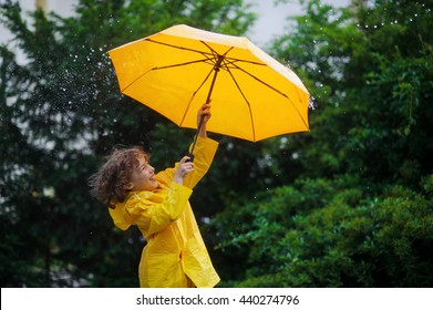 Chappie with a bright yellow umbrella in the warm summer rain. He loves a rain and rejoices. Large rain drops fall on an umbrella dome. Behind the back of the boy a beautiful greens of park.