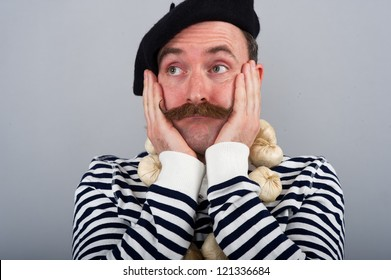 Character portrait of a Frenchman wearing a blue and white hooped top - BRETTON STYLE.  He is wearing a beret, a garlic necklace and has his hands clasping his cheeks in an expression of 'Oh well'