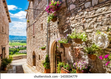 A characteristic alley of the medieval village, with stone and brick houses, plants and flowers on the windows. In Spello, province of Perugia, Umbria, Italy.
