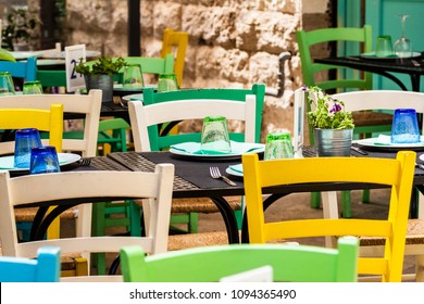 A characteristic restaurant in the streets of Bari, Italy, with tables and colorful chairs.