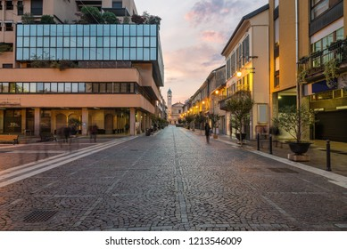 Characteristic street in the historic center of a city in northern Italy. Saronno (corso Italia), province of Varese, Lombardy at sunrise. At the bottom the Church of Saints Peter and Paul