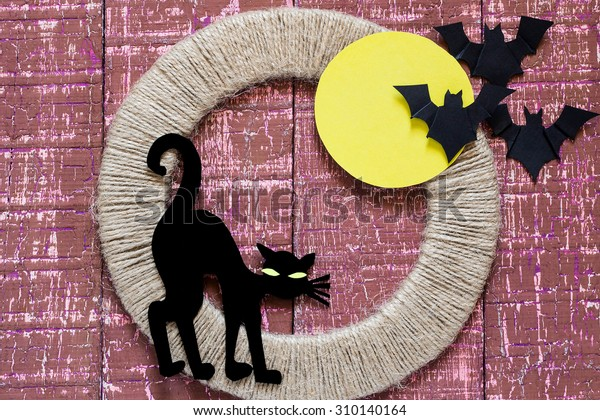 Characters Halloween on burgundy wooden background: black cat out of paper, bats, big yellow moon on jute ring
