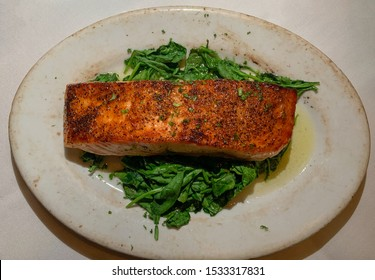 charbroiled king salmon with butter served on a bed of spinach.